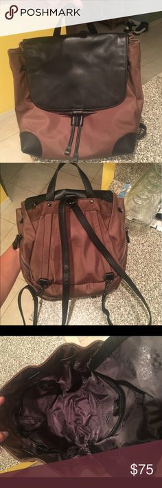 Vince Camuto Nylon and Leather Backpack Two-tone brown and black makes it very versatile and goes with everything! Drawstring with gunmetal detail on flap. Used but still very good condition, inside is exceptionally clean and spotless! Outside of nylon has a couple small water spots, may be able to be cleaned off. Straps are like new, not peeling or cracking at all, and can adjust to either backpack style or cross body handbag. Perfect for shopping hands-free for amusement parks! Open to…