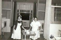 St Joseph ziekenhuis. Ophalen van ontbijtbordjes na een nachtdienst. Links dagelijkse tenue (nachtdienst zat erop), rechts in werkschort (vroegdienst). Aan de blauwe jurk werd een gesteven kraagje geknoopt en aan de korte mouw een wit gesteven boordje.