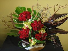 ** 25 roses, green cymbidiums, Manzanita, ti leaves, lily grass and Monstera leaves
