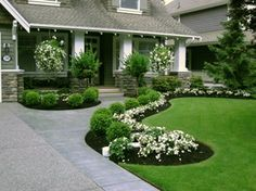 Love the curved flower beds with the boxwoods and flowers. Also, the pillars for the porch are exactly what I want for the house.