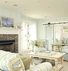Beach Elements - Sliding barn/shutter door. Washed out colors scattered around the room. Water painting above fireplace. Natural elements - stone, baskets, flowers