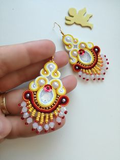 Shiny yellow soutache earrings with milk white cabochon, white pearls and milk white bicones together with red, yellow and gold beads