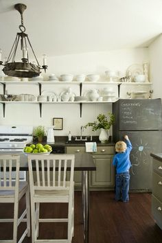 kitchen renovation- Kitchen design by Lauren Liess | cool kitchen with open shelves and a chalkboard over the fridge. Love the chandelier!