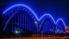 Die Elbbrücken in Hamburg leuchten in blauem Licht.