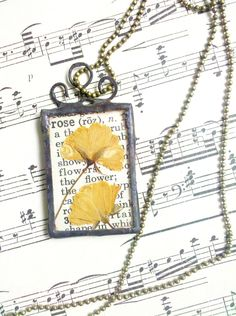 Pressed Yellow Roses Botanical Vintage Style Soldered Glass Necklace    Pressed between two pieces of glass are two tiny yellow roses from my garden. They rest on a piece of vintage dictionary paper with a partial definition of the word rose behind it, and on the back are the matching illustrations. I finished the solder off with patina and a hand hammered scroll to add to the vintage feel :)