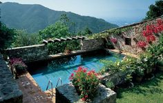 Italian pool surrounded by flowers and rustic stones, overlooking the Tuscan countryside.  Photo: Richard Mandelkorn