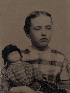 Very early antique photo of little girl and her doll, 1870 - 1880.