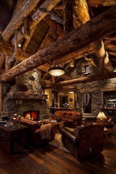 Cabin life - living room with exposed beams, fireplace and leather sofas