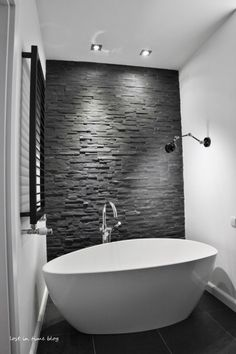 czarny kamień łupek na scianie w łazience,biała owalna wanna wolnostojąca,czarny kinkiet nad wanną