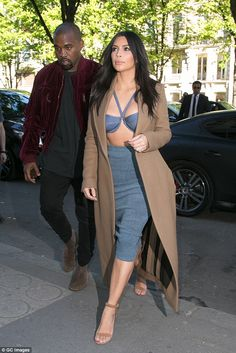 Turning heads: Kim led the way into the Montaigne Market while her rapper husband followed...
