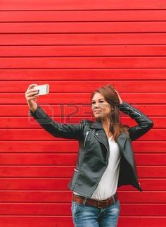 Beautiful young woman in a black leather jacket makes selfie on a red wooden wall