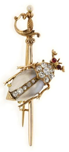 A Victorian moonstone and diamond beetle brooch, the body of the beetle brooch set with cabochon-cut moonstones, the head and central streak of the body set with old brilliant-cut diamonds, estimated to weigh a total of 0.6 carats, with cabochon-cut ruby eyes, all set to a yellow gold back and sword with pearl set to the handle, gross weight 5.4 grams, circa 1890