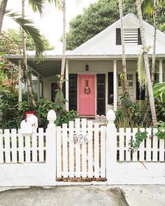 Key West style cottage with a pink door and a picket fence. Beach Cottage Style, Beach Cottage Decor, Coastal Cottage, Coastal Homes, Cottage Homes, Coastal Living, Key West Cottage, Key West House, White Cottage