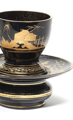 A good Bohemian hyalith cup and trembleuse stand, circa 1825-30 From the Buquoy Glasshouse, the jet-black cup-shaped beaker raised in the middle of a separate base with a reservoir beneath a wide saucer-like rim, gilt with chinoiserie decoration of pavilions, a fence, trees and plants, a solitary Chinese figure and crane-like birds, the interior of the beaker speckled in gold to simulate lacquer, 12.8cm