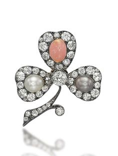 AN ANTIQUE PEARL, CONCH PEARL AND DIAMOND BROOCH  Of trefoil design, each leaf set with a white, a grey or a conch pearl, within an old-cut diamond surround, to the old-cut diamond centre and stem, 19th Century, 4.0 cm