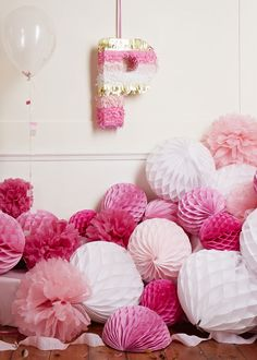 Popping pink tissue pom poms and honeycombs. The personalised letter piñata with glitter tissue is just fab!
