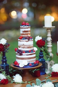 LOVE this naked wedding cake with red and blue details themed for the fourth of July! The white frosting, the strawberries and the blueberries and roses look just stunning! Perfect for a beach wedding!