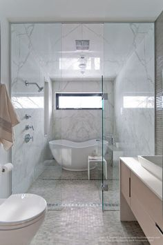 full sheets of 4-by-8 Calacatta marble to create the shower room and balanced it out with a much smaller mosaic tile on the floor and other walls.
