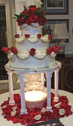 3 %0Atier ivory wedding cake with champagne fondant decorations and fresh red roses, sitting on tiers with fountain underneath. I love this cake.