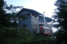 Perched up on a hill in San Juan Island, Washington, this rustic cabinhas two towers. The entire cabin is a total of 672 sq. ft. The towers are connected by a lower level open living and dining ar…