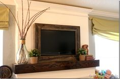 rustic mantel and framing out a tv with reclaimed wood now if we could figure out how to put a removable pic over the tv....maybe a window shade of of some sort?