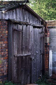 Garden shed with brick walls and an old weathered wooden door and front facade - free stock photo from www.freeimages.co.uk