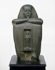 """Naophorous Block Statue of a Governor of Sais, Psamtik[seneb] Period: Late Period, Saite Dynasty: Dynasty 26 Date: 664–525 B.C.  This statue represents a governor of the Saite nome (district ) in the western Nile Delta, and was intended for a temple in Sais, its capital city. The temple, called the """"House of the Bee,"""" was dedicated to Osiris, who is represented standing in a shrine on the front of the statue."""