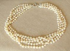 Five strands of fresh water pearls intertwine together.  Handmade by a rescued lady in Asia PLEASE NOTE THAT ALL SALE ITEMS ARE SENT IN A POUCH (GIFT BOXES ARE UNAVAILABLE).