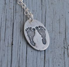 This is one of my favorite pieces of jewelry.  They actually took a scan of mason's feet and created a stamp from them to make one like this for me.  It Rocks.    Your baby/child's footprints in fine silver