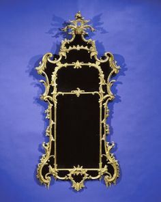 "A Superb Pair of George II Giltwood Pier Mirrors,     CIRCA 1755,     Height: 80"" Width: 39"".         The divided rectangular plate enclosed by shaped border plates, set within a surround elaborately carved with c-scrolls, rockwork, and floral garlands; surmounted by an acanthus leaf-carved clasp."