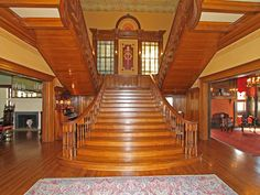 Staircase in the Grand Entry all - directly across from the front door. The doorway seen to the left enters into the Dining Room.  The doorway seen to the right of the stairs is the entry to the Billiard Room. Both rooms can be closed off from the Grand Entry Hall using the hardwood pocket doors hidden in the walls.  Note the beautiful stained glass windows on the landing.