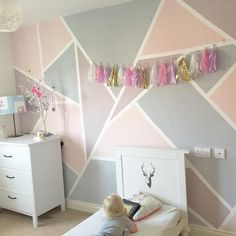 Girls room with geometric shape wall painted in pink and purple