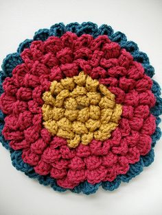 Fancy Flower potholder. Make it bigger and it would be a great pillow.