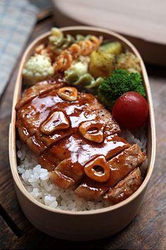 Bento box featuring garlic steak over rice, cauliflower macaroni salad, and pan-fried new potatoes