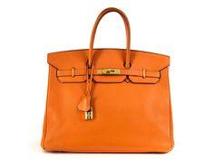 Ca. 25 x 35 x 18 cm. Orangefarbene Togo-Lederhandtasche mit goldfarbenen Beschlägen. Innenraum mit gleichfarbigem Leder ausgeschlagen, mit einem...