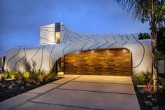 """Venice's """"Wave House"""" is striking from the street. Beyond its atypical shape, all rounded edges and undulating roof, the residence by designer Mario Romano is particularly eye-catching because it's """"cloaked"""" in a white aluminum and cedar blocks."""