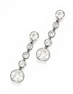 PAIR OF PLATINUM AND DIAMOND PENDANT-EARRINGS. Set with two old European-cut diamonds weighing approximately 3.05 carats, suspended by eight smaller old European-cut diamonds weighing approximately 2.25 carats; circa 1925.