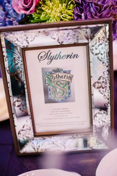 Harry Potter inspired table names for wedding reception. The picture frame centerpiece was a DIY project. I purchased the frames from Big Lots and found the picture online. Picture contains a description of the Harry Potter reference, and a quote from the book that includes the reference.