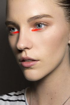 """<p><strong>The Look:</strong> A Brushstroke of Neon Liner</p> <p><strong>How-To:</strong> The idea for the conceptual makeup at Peter Som—sort of Warholian pop art meets warrior princess—came from the vibrant shade of orange running throughout the collection. """"We decided to do a brushstroke of neon orange color swooped out under the eyes,"""" says makeup artist Yadim. """"It's super easy to do and it's not supposed to be perfect."""" Here's the coolest part: He used lipstick—not eyeliner—to do it…"""