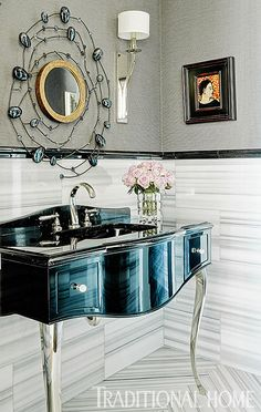 A custom striped floor tile is laid in a herringbone pattern to make a big impact in the small space. The vanity cabinet and sink from Devon and Devon sits on elegant silver legs.