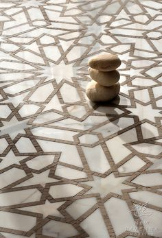 Pretty  Castilla, a natural stone waterjet and hand cut mosaic shown in Jura Grey honed and Calacatta Tia polished, is part of the Miraflores Collection by Paul Schatz for New Ravenna Mosaics.