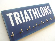 The wall decal lettering on the race medals display reads 'TRIATHLON', so there will be no doubt that you are indeed an athlete person. The rustic charm of the triathlon display makes it perfect for any room and any wall.
