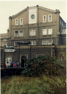 https://flic.kr/p/7eumPL | Zittau - Oybin - Jonsdorf Schmalspurbahn. Bahnhof Zittau. 10 November 1989 | A fascinating illumating sign with steam locomotive on top of it - perhaps also illuminated from within - points the way to the adjacent Narrow gauge station in Zittau. The hikers are heading for the Main Line DR station which looks really quite ugly.  TIme  is about 10.32 am. and the train for Oybin will be departing shortly. Must hurry.
