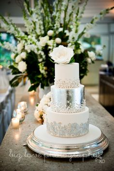 silver wedding cake. At the Reception, any where can be Your Cake Table-here a counter decorated with candles and flowers serves well.