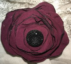 Deep maroon flower clip with a black sparkly jewel center!