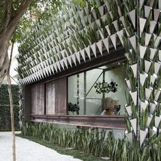 Furniture showroom featuring a facade covered with thousands of plant-filled vases.