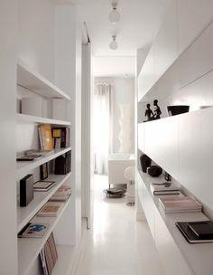 Dans un appartement tout blanc, le couloir a été aménagé d'étagères et de placards pour gagner de la place et des rangements