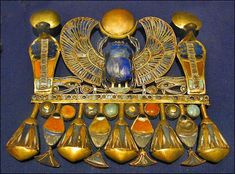 """Winged scarab of Tutankhamun with semi-precious stones. This pectoral is composed of Tut's Prenomen name: """"NebKheperU-Ra"""", the hieroglyphs of: Basket, Scarab-(in Plural-strokes), and Re. Objets Antiques, Egypt Jewelry, Ancient Egyptian Jewelry, Art Ancien, Art Antique, Sacred Symbols, Tutankhamun, Ancient Artifacts, Ancient Civilizations"""