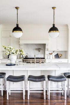 Gorgeous kitchen features white shaker cabinets paired with white marble…