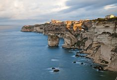 Bonifacio, Corsica. Corsica is an island in the Mediterranean Sea belonging to France. It is located west of the Italian Peninsula, southeast of the French mainland, and north of the Italian island of Sardinia. Mountains make up two-thirds of the island, forming a single chain.
